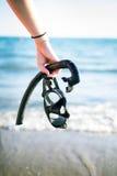 WomanÂs snorkel och maskeringar för handuppehälle på en sandig strand konkurrensar som dyker pölsportar som simmar vatten snorkel Royaltyfri Bild