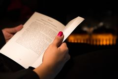 Woman Reading  a Book by Fireplace. Woman's Hand Holding a Book by a Fireplace Royalty Free Stock Photo