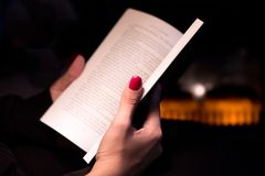 Close Up Woman's Hand Holding a Book by a Fireplace. Woman's Manicured Hand Holding a Book by a Fireplace Stock Images
