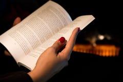 """Womanβ Hand â die '¬â """"¢s een Boek houden door een Open haard Royalty-vrije Stock Foto"""