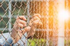 Woman& x27 το χέρι του s επίασε ένα κλουβί σιδήρου σε ισχύ της κράτησης για να αναμείνει την ελευθερία Ελαφριά έκθεση στοκ εικόνα