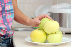 Woman& x27 το χέρι του s παίρνει ένα μήλο από το πιάτο Στοκ εικόνα με δικαίωμα ελεύθερης χρήσης