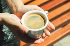 Woman& x27; рука s с чашкой горячего кофе Стоковая Фотография RF