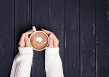 Woman& x27; 在拿着咖啡的毛线衣的s手 库存照片