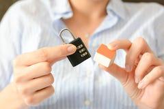 woman& x27特写镜头; s递拿着一个小模式房子和暗号锁 库存图片