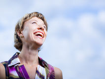 Woman. Laughing woman on a blue sky background - shallow DOF Royalty Free Stock Photo
