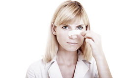 The woman. Face of young woman with sticking plaster on nose on the white background Royalty Free Stock Photo
