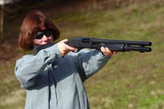 Woman with a 12 gauge shotgun. A white female aiming a 12 gauge shotgun Stock Photography