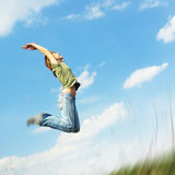 Woman. Jumping young woman over blue sky background Royalty Free Stock Photo