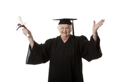 Beauitiful Caucasian woman in a black graduation gown with diploma Stock Images