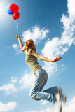 Woman. Flying young woman with balloons over blue sky background Stock Images