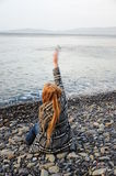 Woman. A woman throws stones into sea Stock Image