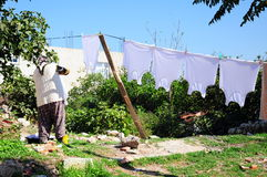 Woman. A woman hangs clothes on her garden Stock Image