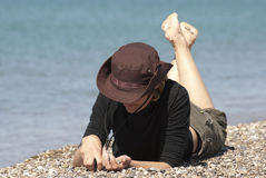Woman. Young woman lies on a beach, the woman collects stones, the person is hidden Stock Photos