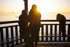 Woman and 2 Kids on Dock House Watching Sunset Royalty Free Stock Photo