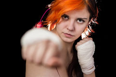 Woman. Yound beautiful redhead colored woman posing as kickboxer in studio, black  background Stock Photo