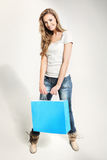 Woman. Beautiful Young blonde woman with blue carrier-bag Royalty Free Stock Image