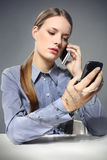 Woman. Long hair Beautiful Young blonde woman with two mobile phones and Prickly wire Royalty Free Stock Photos