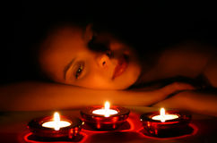 Woman and 3 candles. Woman looking on 3 candles Royalty Free Stock Image