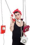 Woman with 3 phones. Woman with red kerchief holding many phones which are hanging Royalty Free Stock Images