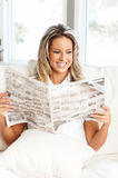 Woman. Young  woman reading a newspaper  in the comfortable apartment Royalty Free Stock Images