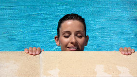 Woman. Girl in the pool with hands and head outside the water stock photo