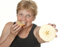 Woman (67 years old) eating an apple Stock Photos