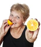 Woman (67 years old) eating orange Stock Photo