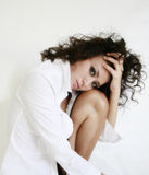 Woman. Head resting on knee hand running through hair Royalty Free Stock Photos