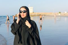 Woman in abaya using phone on the beach. Woman in abaya having a phone call on the beach Royalty Free Stock Photography