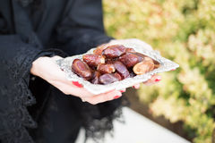 Woman in abaya is offering dates Royalty Free Stock Photography