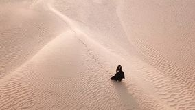 A woman in abaya walking in the desert. stock photos