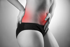 Woman with abdominal and back pain. Pain in the human body. Black and white photo with red dot Stock Images