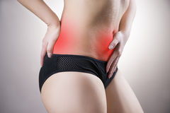 Woman with abdominal and back pain. Pain in the human body. On a gray background with red dot Stock Photos