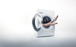Woman absorbed by washing mashine. Conceptual bright photo of a woman absorbed by household duties Stock Images