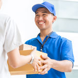 Woman accepting a delivery of cardboard boxes from deliveryman Royalty Free Stock Images