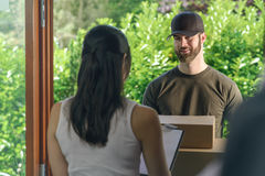 Woman accepting a delivery of two cardboard boxes Stock Photos