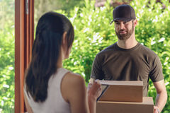Woman accepting a delivery of two cardboard boxes Royalty Free Stock Photography