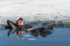 The woman accepts the curative mud baths on lake Elton. Stock Image