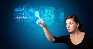 Woman accessing hologram with fingerprint. Woman accessing modern hologram personal database with fingerprint identification royalty free stock photos