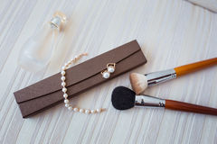 Woman accessories close up: make up brush, earrings, bracelet and perfume. Stock Photo