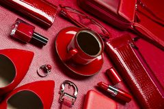 Woman accessories and coffee. Woman red accessories with coffee, cosmetic, jewelry, gadget and other luxury objects on leather background, fashion industry royalty free stock images