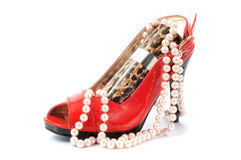 Woman accessory. Red woma shoe with perfume and pearls necklace Stock Image