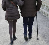 woman accompanies the older gentleman with walking stick Royalty Free Stock Photo