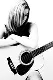 Woman with accoustic guitar. Thirty something woman sitting on stule leaning on accoustic guitar looking down Royalty Free Stock Images
