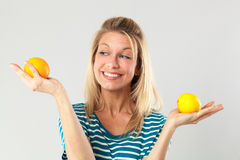 Woman with acidic fruits held in both hands for beauty diet. Natural vitamins concept - smiling young blond woman balancing acidic fruits held in both hands for stock image