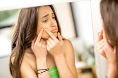 Woman with acne in the bathroom. Young sad woman squeezing acne looking at the mirror in the bathroom royalty free stock photo
