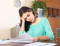 Woman acquainted with documents. Sad woman with documents at home interior royalty free stock photo