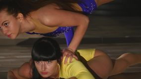 Woman acrobat sits on a string, the other stands on her arms from above stock video