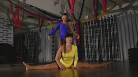 Woman acrobat sits on a string, the other stands on her arms from above stock footage